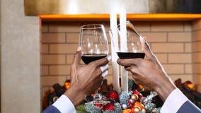 Ferier, nytt år och berömbegrepp Manliga händer som klirrar exponeringsglas av rött vin på jul Mysigt brandställe på lager videofilmer