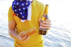 Feriesammansättning med åtskilliga flaskor av öl och varmkorvar, amerikanska flaggan Fira självständighetsdagen av USA Royaltyfri Bild