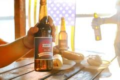 Feriesammansättning med åtskilliga flaskor av öl och varmkorvar, amerikanska flaggan Grupp människor som firar självständighetsda Arkivbilder