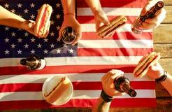 Feriesammansättning med åtskilliga flaskor av öl och varmkorvar, amerikanska flaggan Grupp människor som firar självständighetsda Royaltyfri Foto