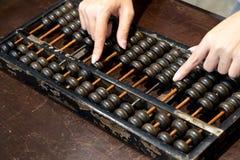 Fermé de la main de femme d'affaires qui calculent avec l'abaque en bois Photographie stock libre de droits