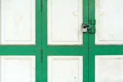 Fermé sur la porte en bois blanche et verte de vintage avec la serrure argentée photos stock