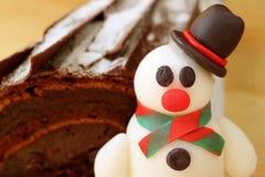 Fermé vers le haut d'un massepain adorable de bonhomme de neige avec du chocolat brouillé Yule Log Cake à l'arrière-plan images stock