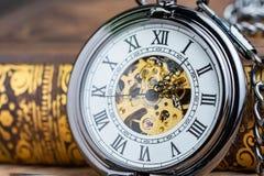 Fermé vers le haut de la montre de poche de vintage sur le livre utilisant comme le symbole de temps ou le b photo stock