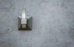 Fermé vers le haut du métal balayé vêtez le crochet monté sur le mur moderne de ciment images stock
