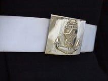Fermaglio d'ottone brillante sulla cinghia bianca del marinaio fotografie stock libere da diritti