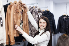Fermale customer choosing jacket at store Royalty Free Stock Image