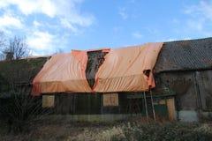 Ferme abandonnée en Hollandes avec la feuille orange dans la tentative d'empêcher d'entrer la pluie photo stock