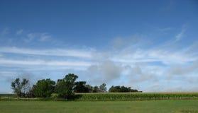 Ferme avec des arbres et des nuages de ciel bleu Images libres de droits