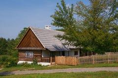 Ferme boisée et un porche couvert par le bord d'un toit Images stock