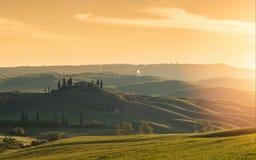 Ferme, collines vertes, arbres de cyprès en Toscane au lever de soleil Photographie stock libre de droits