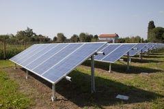 Ferme d'énergie électrique d'écologie avec la batterie de panneau solaire dans f vert Photo libre de droits
