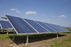 Ferme d'énergie électrique d'écologie avec la batterie de panneau solaire dans f vert Photographie stock