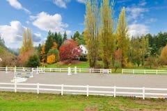 Ferme de cheval avec la barrière blanche et les feuilles colorées de chute. photo libre de droits
