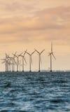 Ferme de groupe électrogène de turbines de vent le long de mer de côte Photographie stock libre de droits