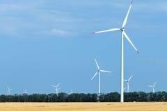 Ferme de turbine de vent au-dessus de la terre utilisée pour l'agriculture Image libre de droits