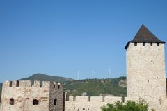 Ferme de vent roumaine avec la turbine et les moulins à vent de vent faisant face à un vieux château situé du côté serbe du Danub Images stock