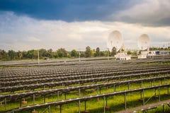 Ferme solaire de large échelle avec les antennes paraboliques sous dramatique Photographie stock