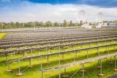 Ferme solaire de large échelle avec les antennes paraboliques sous dramatique Photos stock