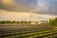 Ferme solaire de large échelle avec les antennes paraboliques sous dramatique Images stock