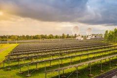 Ferme solaire de large échelle avec les antennes paraboliques sous dramatique Photo libre de droits