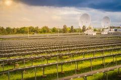 Ferme solaire de large échelle avec les antennes paraboliques sous dramatique Photographie stock libre de droits