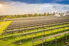 Ferme solaire de large échelle avec les antennes paraboliques sous dramatique Images libres de droits