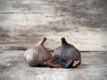 Fermented black garlic bulbs and cloves. Black garlic caused by a fermentation process of several weeks Royalty Free Stock Photos