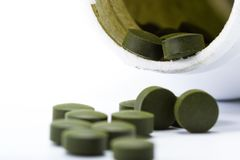 Fermented chlorella tablets. Close up of a group of fermented chlorella tablets isolated on a white background Stock Images