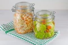 Fermented preservó concepto vegetariano de la comida Col, bróculi, caulie, tarros de cristal amargos de la chucrut en el fondo bl imágenes de archivo libres de regalías