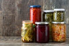 Fermented preservó verduras en el tarro aislado en la madera Imagen de archivo
