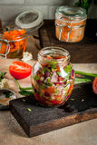 Fermented preserved  food. Concept of a fermented meal. Home canned food and billets. Vegan food. Vegetables. Cans of canned salsa, sauerkraut, marinated carrots Stock Image