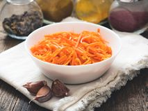Fermented vegetables, Korean carrots. Asian spicy salad in white plate on wooden background stock photography