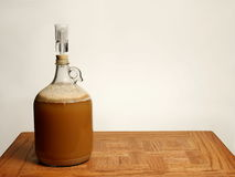 Fermenting Homebrew Beer. A one gallon growler used for primary fermentation of homebrew beer is shown on an Oak table Stock Photos