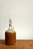 Fermenting Homebrew Beer. A one gallon growler used for primary fermentation of homebrew beer is shown on an Oak table Royalty Free Stock Photography