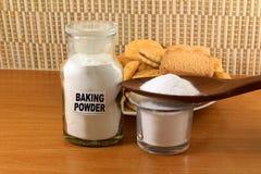 Fermento em pó em um frasco de vidro e em uma colher de madeira com cookie e pão Imagem de Stock