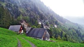 Fermes de bétail alpines et architecture traditionnelle sur les pentes du sud de la gamme de montagne de Churfirsten image stock
