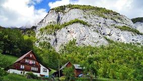 Fermes de bétail alpines et architecture traditionnelle sur les pentes du sud de la gamme de montagne de Churfirsten image libre de droits