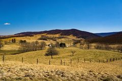 Fermes en vallée bleue d'herbe photos stock
