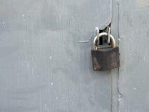 Fermez à clef à une porte sale en métal Image stock