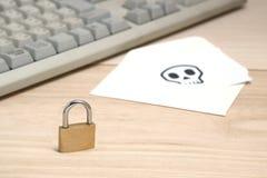 Fermez à clef devant l'enveloppe avec le crâne écrit sur le clavier d'ordinateur de repos de carte Photographie stock