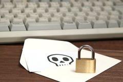 Fermez à clef devant l'enveloppe avec le crâne écrit sur le clavier d'ordinateur de repos de carte Images libres de droits