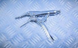 Fermez à clef les pinces de mâchoire sur le conce creusé des rigoles de construction de fond en métal Photographie stock