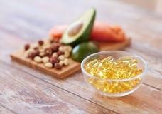 Fermez d'Omega 3 capsules et nourritures sur la table Images libres de droits