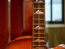 Fermez de l'les piqûres de fingerboard's sur une guitare acoustique avec photographie stock libre de droits