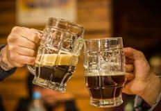 Fermez des amis masculins heureux faisant tinter avec des tasses de bière dans le bar Images libres de droits