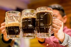 Fermez des amis masculins heureux faisant tinter avec des tasses de bière dans le bar Image libre de droits