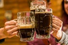 Fermez des amis masculins heureux faisant tinter avec des tasses de bière dans le bar Photographie stock