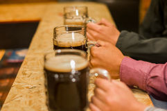 Fermez des amis masculins tenant une bière de métier dans le bar Photos stock
