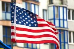 Fermez- du nous drapeau contre l'horizon de ville images stock
